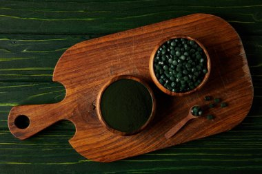 top view of cutting board with wooden spoon, bowls with spirulina powder and spirulina in pills on green wooden table