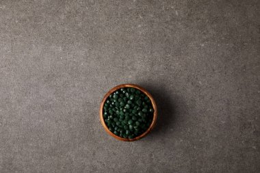 top view of wooden bowl with pile of spirulina pills on stone table