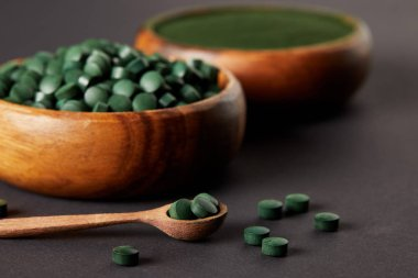 selective focus of wooden spoon and bowls with ground spirulina and spirulina in pills on grey table