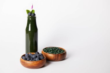 bottle of spirulina smoothie with mint leaves and drinking straw, bowls with blueberries and spirulina pills on grey background