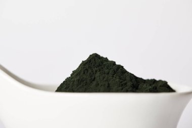 close up view of spirulina algae powder in bowl isolated on grey background