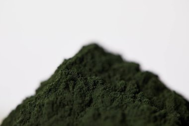 selective focus of spirulina algae powder isolated on grey background