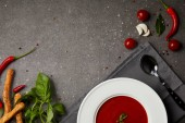 top view of tasty tomato soup in plate on napkin on grey table