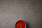 top view of plate with tasty tomato soup with basil on grey table with scattered spices
