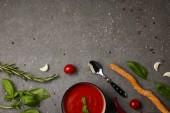 pohled shora desky s chutnou rajskou polévku a čerstvá rajčata na šedý stůl
