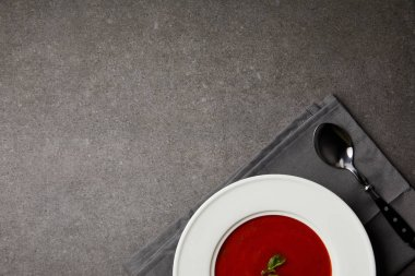 top view of tasty tomato soup in plate and spoon on grey napkin on grey table