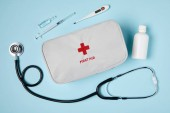 Fényképek top view of white first aid kit bag with stethoscope and medicines on blue surface