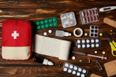 Fotografie top view of first aid kit bag with various medicines on wooden tabletop