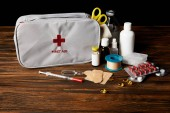 Fényképek close-up shot of first aid kit with different medicines on wooden tabletop and on black