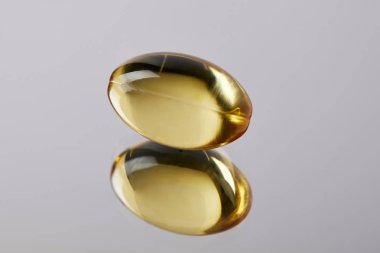 close-up shot of healthy omega fish hat supplement capsule on reflective surface