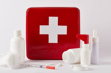 First aid kit box with blank medical bottles, syringe and cotton swab on white stock vector