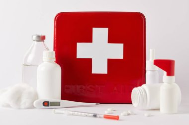 Close-up shot of red first aid kit box with different medical bottles and supplies on white stock vector