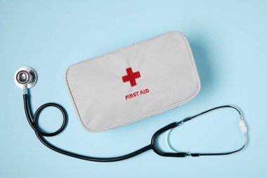 top view of white first aid kit bag with stethoscope on blue surface