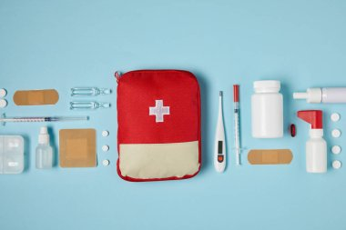 Top view of red first aid kit bag on blue surface with medical supplies stock vector