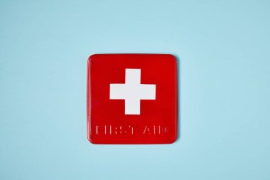 Top view of red first aid kit box on blue surface stock vector