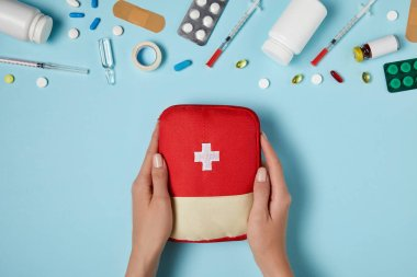 cropped shot of woman holding first aid kit bag over blue surface with various medicines
