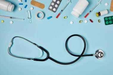 top view of stethoscope and various medicines on blue surface