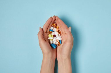 cropped shot of woman holding heap of pills over blue surface