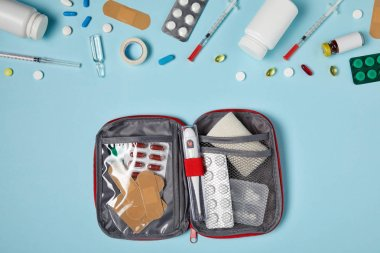 top view of opened first aid kit bag on blue tabletop