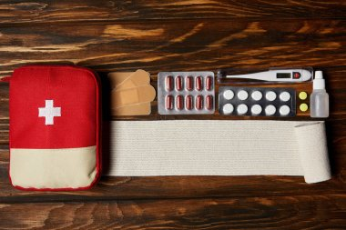 top view of first aid kit bag with various pills, bandage and electric thermometer on wooden tabletop