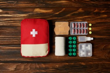 Top view of first aid kit composed with various pills and bandage on wooden tabletop stock vector