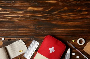 top view of first aid kit with different medicines on wooden tabletop