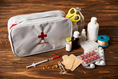close-up shot of first aid kit with various medical supplies on wooden tabletop