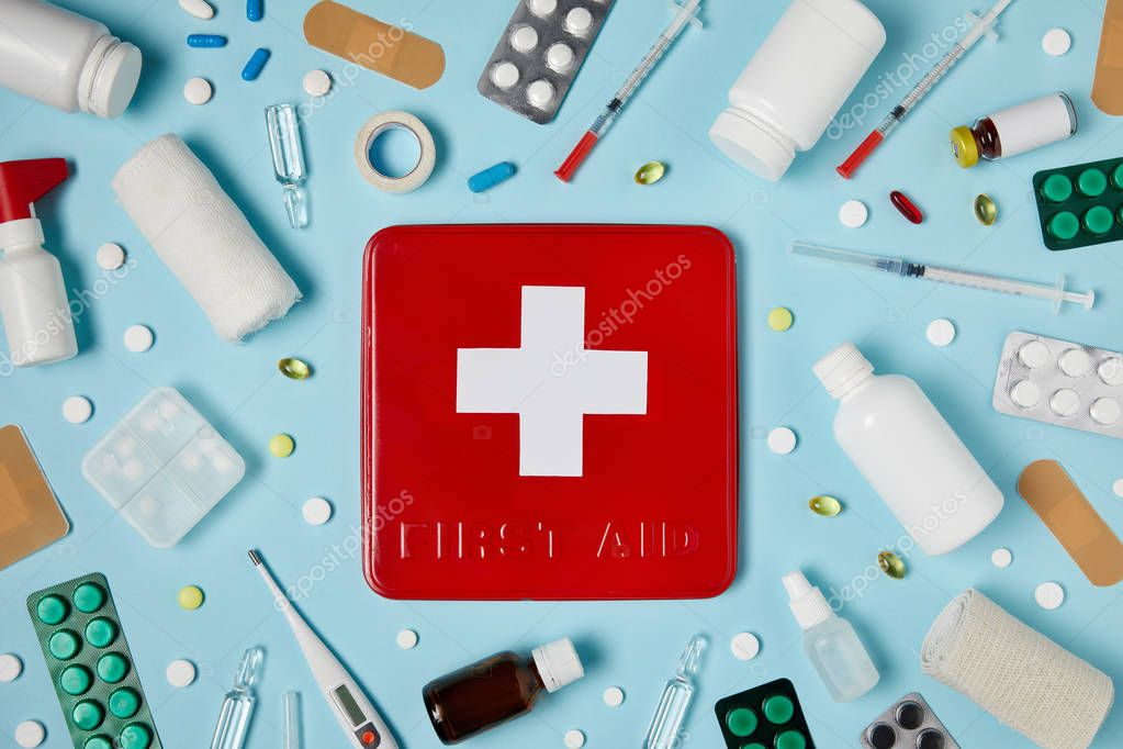 Top view of red first aid kit box on blue surface surrounded with different medicines stock vector