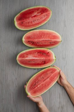 partial view of male hands and fresh watermelon slices on grey wooden tabletop