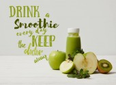 Fotografie green detox smoothie with apples, kiwi and mint and on white wooden surface, drink smoothie everyday keep doctor away inscription