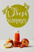 Fotografie bottle of detox smoothie with apples and carrots on white wooden surface, fresh summer inscription