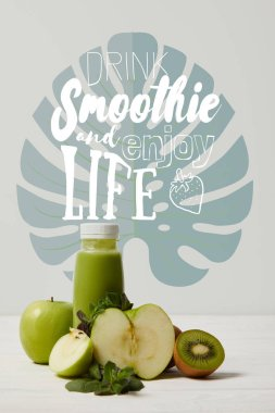 green detox smoothie with apples, kiwi and mint and on white wooden surface, drink smoothie and enjoy life inscription