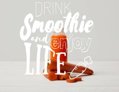 bottle of detox smoothie with carrots on white wooden surface, drink smoothie and enjoy life inscription