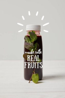 bottle of detox smoothie with mint on white wooden surface, made with real fruits inscription