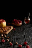 Fotografie hazelnuts with apple and raspberries on black wooden table