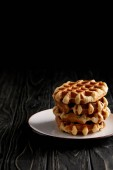 Photo stack of freshly baked belgian waffles on plate on black wooden table