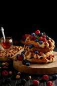 Photo delicious belgian waffles with berries and hazelnuts on black wooden table