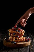 Photo cropped shot of woman touching stack of belgian waffles with berries on black wooden table