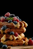 Photo delicious stacked belgian waffles with berries on wooden cutting board on black