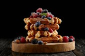 Photo freshly baked stack of belgian waffles with berries on wooden cutting board on black