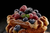 Photo close-up shot of delicious belgian waffles with berries spilled with sugar powder on black