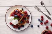 Photo top view of delicious belgian waffles with berries and ice cream on white wooden table
