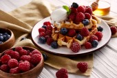 Photo fresh belgian waffles with berries and ice cream on white wooden table