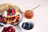 Photo delicious belgian waffles with berries and honey on white wooden table