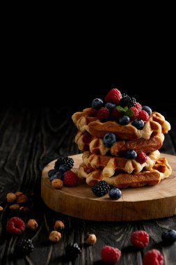 stack of belgian waffles with berries on wooden cutting board on black