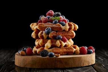 freshly baked stack of belgian waffles with berries on wooden cutting board on black