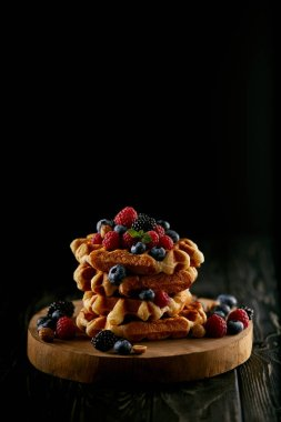 tasty stacked belgian waffles with berries on wooden cutting board on black