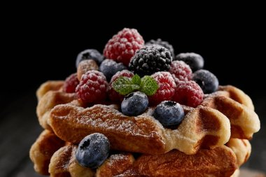 close-up shot of delicious belgian waffles with berries spilled with sugar powder on black