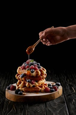 cropped shot of woman pouring honey onto stack of belgian waffles on black wooden table
