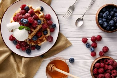 freshly baked belgian waffles with honey, ice cream and berries on white wooden table